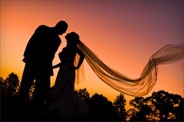 Siloutte of couple with blowing veil in sunset